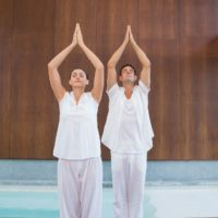 Peaceful couple in white doing yoga together in health spa